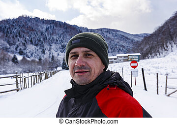 portrait of a man in a winter landscape in the mountains