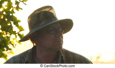 Portrait of a man in dark glasses and khaki protective hat....