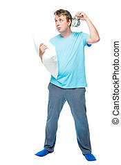 Portrait of a man in full length with an alarm clock and a pillow on a white background