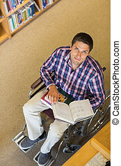 Portrait of a man in wheelchair reading a book in library