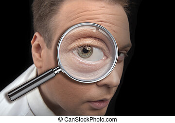 portrait of a man looking in a magnifying glass