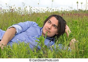 portrait of a man lying on grass