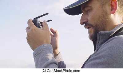 Portrait of a man operating a drone quadrocopter - Close up...