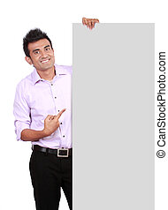 man peeking behind empty white billboard