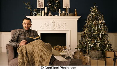 Portrait of a man reading book to the camera on Christmas evening.