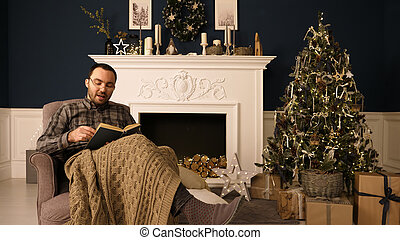 Portrait of a man reading book to the camera on Christmas evening. Professional shot in 4K resolution. 015. You can use it e.g. in your christmas, commercial video,new year, presentation, broadcast