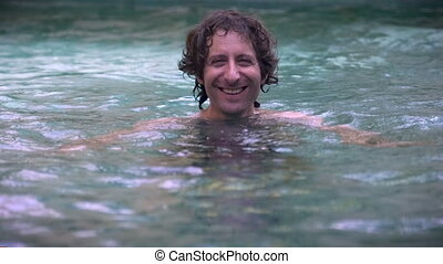 Portrait of a man smiling in a swimming pool in slow motion