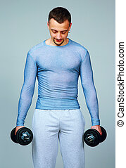 Portrait of a man standing with dumbbells on gray background