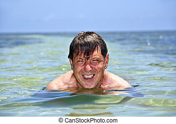 portrait of a man swimming in the crystal clear ocean