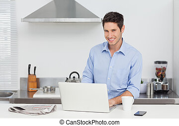 Portrait of a man using a laptop in the kitchen