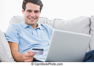 Portrait of a man using his credit card to purchase online