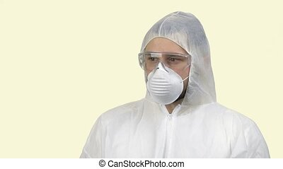 Portrait of a man wearing antiviral respiratory mask looking aroung in panic. Fear of coronavirus. Isolated on yellow background.