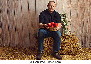 man with basket of red apples in a barn
