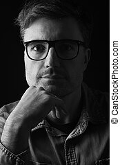 portrait of a man with glasses on black background