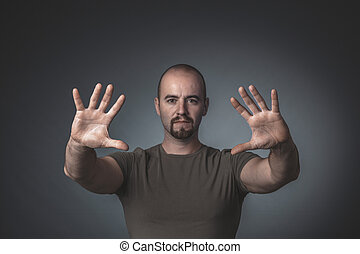Portrait of a man with hands outstretched ahead of him.