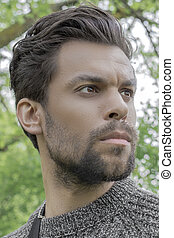 Portrait of a man with stubble on his face and a confident look to the side
