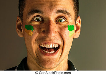 Portrait of a man with the flag of the Brazil painted on him face.