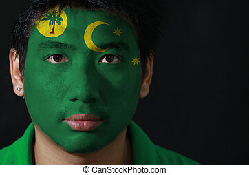 Portrait of a man with the flag of the Cocos (Keeling) Islands painted on his face on black background, a palm tree on a gold disc, crescent and southern cross on green.