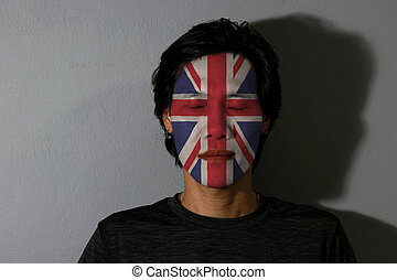 Portrait of a man with Union jack flag painted on his face and close eyes with black shadow on grey background. The concept of sport or nationalism.