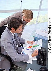 Portrait of a manager and her secretary looking at a graph
