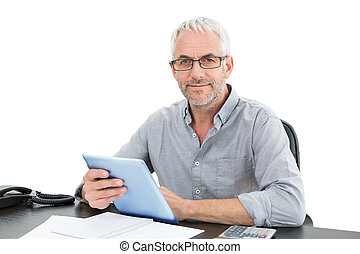 Portrait of a mature businessman with digital tablet and telephone at desk against white background