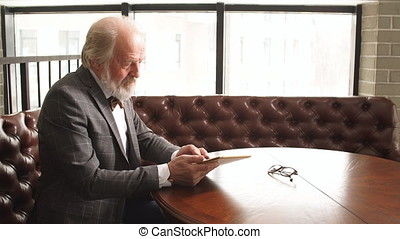 Portrait of a mature businessman with digital tablet.