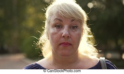 Portrait of a sad mature overweight woman at sunset