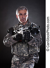 Portrait Of A Mature Soldier Aiming With Gun