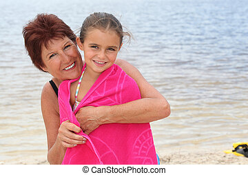 Portrait of a mature woman and a little girl by the seaside