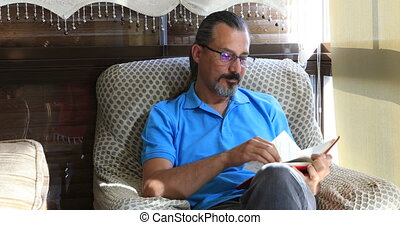 Portrait of a mid adult brunette man sitting on a sofa and reading a book at home interior