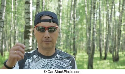 Portrait of a middle-aged man, an athlete in sports glasses. On a sunny day, in the park.