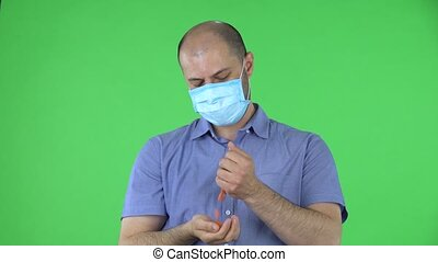 Portrait of a middle aged men in medical mask pours medicine from hand to hand. Balding male in blue shirt posing on green screen in the studio. Close up.
