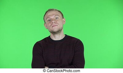 Portrait of a middle aged men listens attentively, nods his head approvingly, points a finger yes, you are right, for sure. Unshaven male in sweater posing on a green screen in the studio. Close up.
