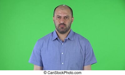 Portrait of a middle aged men looking at the camera in anticipation and then very upset. Balding male with beard in blue shirt posing on green screen in the studio. Close up