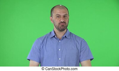 Portrait of a middle aged men looking at the camera shows a thumbs up gesture with both hands. Balding male with beard in blue shirt posing on green screen in the studio. Close up