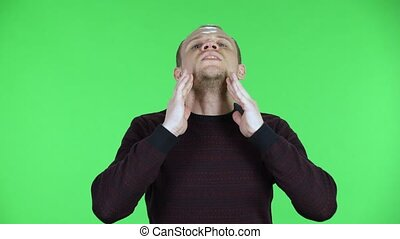Portrait of a middle aged men suffering from headache from fatigue . Unshaven male in a black red sweater posing on a green screen in the studio. Close up.