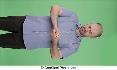 Portrait of a middle aged men treats their hands with disinfectant. Balding male with beard in blue shirt posing on green screen in the studio. Slow motion. Vertical video