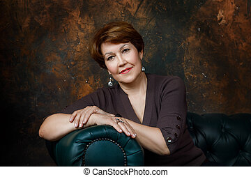 Portrait of a middle aged woman sitting on a sofa