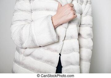 Portrait of a model in fur white coat close-up