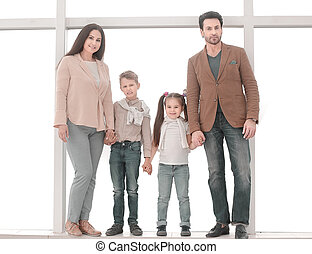 portrait of a modern family standing near a large window