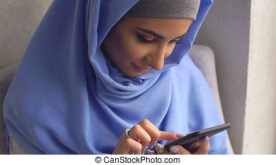 Young woman in hijab dials message on mobile phone. -...