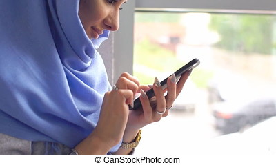 Portrait of a modern Muslim woman close-up. Slow motion. Young woman in hijab dials message on mobile phone.