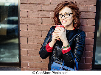 Portrait of a modern young woman with coffee cup in hands,  urba