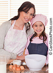 Portrait of a mother and her daughter baking