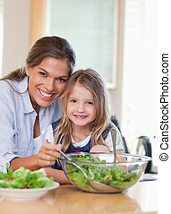 Portrait of a mother and her daughter preparing a salad