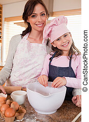 Portrait of a mother baking with her daughter