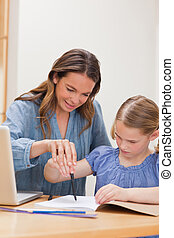 Portrait of a mother helping her daughter doing her homework
