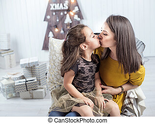 Portrait of a mother kissing a daughter