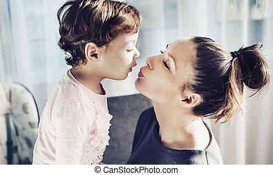 Portrait of a mother kissing her beloved child