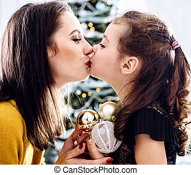 Portrait of a mother kissing her daughter holding glass balls
